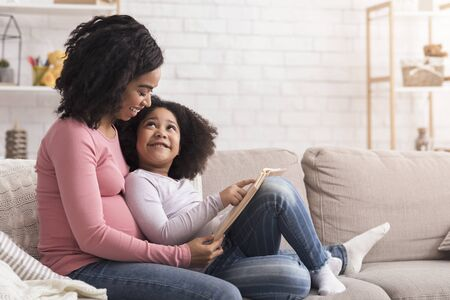 Preschool Development Concept. Little Black Girl Reading Book With Her Pregnant Mom At Home, Sitting On Couch And Smiling, Copy Space