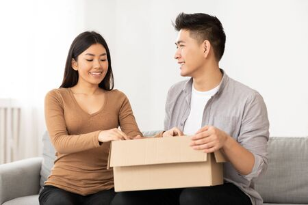 Changing Apartments. Filipino family sitting on sofa and unpacking cardboard boxes, free space Stock Photo