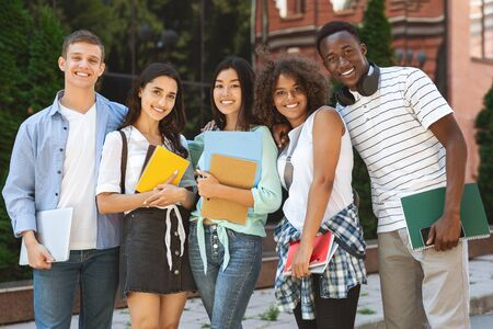 Group portrait of multicultural college students posing in campus with workbooks in hands Banque d'images