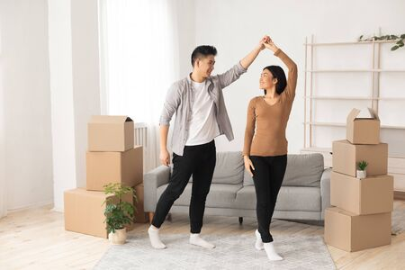 Celebrating Moving Day. Happy young asian tenants dancing among unpacked boxes in new home