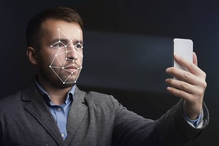 Unlocking smartphone with face recognition. Man with scanning mesh on face against black background
