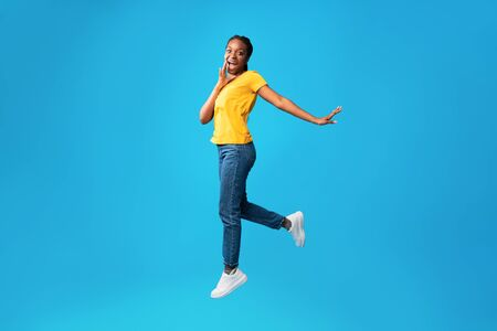 Cheerful African Woman Shouting Jumping In Air Holding Hand Near Mouth On Blue Background. Studio Shot, Free Space