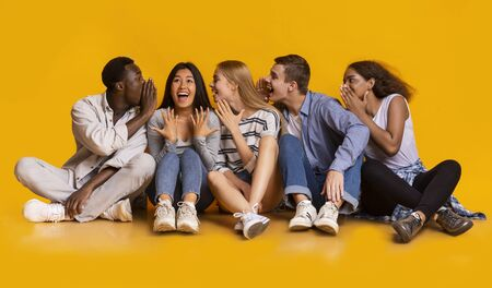International friends sitting in row on floor, sharing gossips over yellow studio background, student lifestyle, panorama