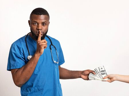 African male therapist taking bribe and holding finger on lips, white background, copy space