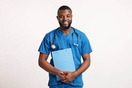 Handsome black guy therapist in blue uniform making check up, holding medical chart over white studio background