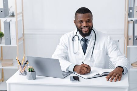 Smiling black male doctor working with laptop in modern office, taking notes, copy space Reklamní fotografie
