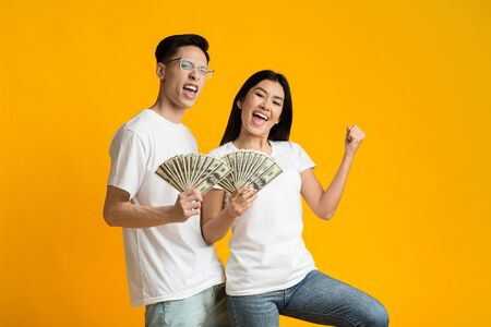 Young happy rich asian couple holding bunch of money over yellow studio background
