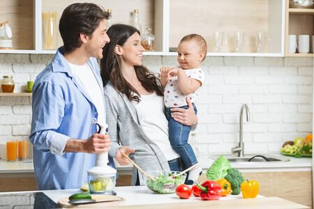 Cooking together. Mom making salad for adults, daddy making apple puree for baby son at kitchen, empty space Reklamní fotografie
