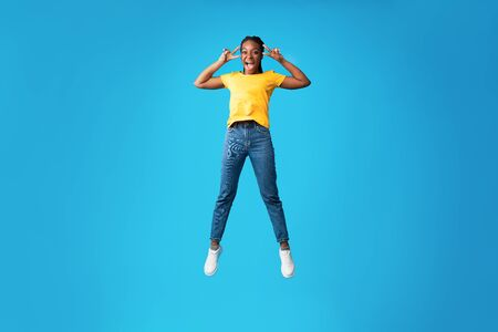 Joy Of Victory. Cheerful African American Girl Jumping Gesturing V-Sign Over Blue Studio Background. Full Length, Empty Space