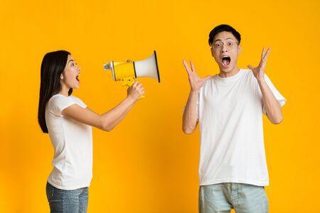 Asian girl shouting exciting news to shocked boyfriend using megaphone, yellow background Foto de archivo