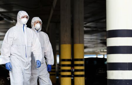 World epidemic of coronavirus. Men in virus protective suits patrol the city while quarantine, copy space 版權商用圖片