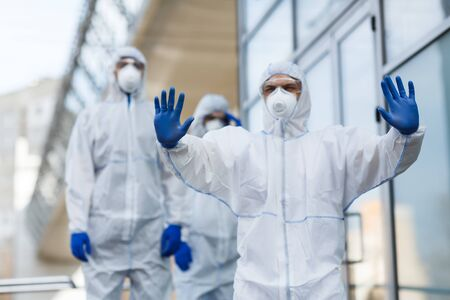 Stop, no panic, please. Man in virus protective suit stopping crowd from going forward, gesturing