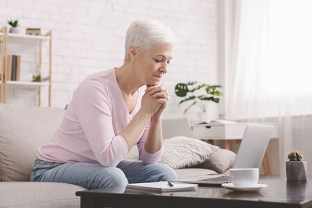 Self-isolation at home. Sad senior lady looking at laptop with perplexity, empty space