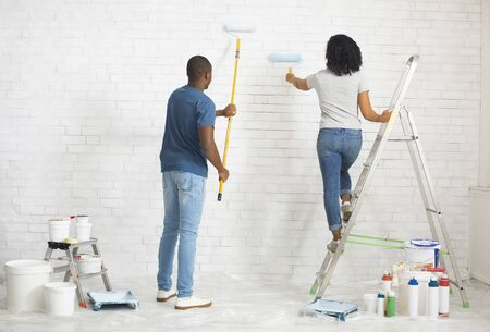 African american girl on stepladder and guy paints wall with roller, free space Standard-Bild