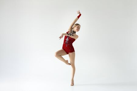 Graceful gymnast of ballet dancer in red leotard performing beautiful dance on white background, empty space