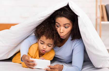 African Mom And Little Girl Playing Mobile Games On Smartphone Lying In Bed Having Fun Together. Selective Focus