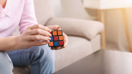 Kharkiv, Ukraine - January 14, 2019: Rubiks cube in hands of mature woman, stay at home concept, free space