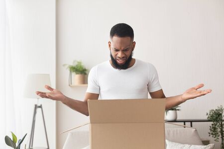 Wrong item. Surprised african american millennial man opened box and spreads his hands