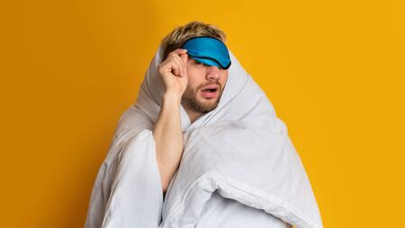 Funny guy wrapped in blanket takes off his sleep mask and squints