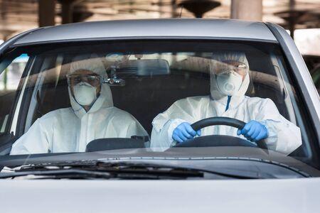 Two men in a car, both wearing virus protective suits and masks, coronavirus epidemic, quarantine, copy space Reklamní fotografie