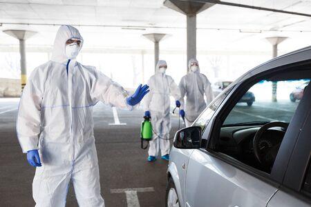 Men in hazmat suits stopping and disinfecting cars of coronavirus cells, world epidemic, quarantine Foto de archivo