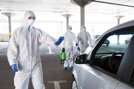 Men in hazmat suits stopping and disinfecting cars of coronavirus cells, world epidemic, quarantine