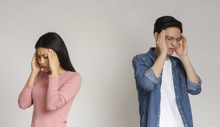 Asian young couple having headache cause of fight, touching their heads, panorama with copy space