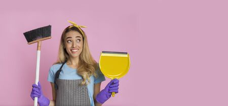 Young beautiful woman with broom and shovel smiles on pink background