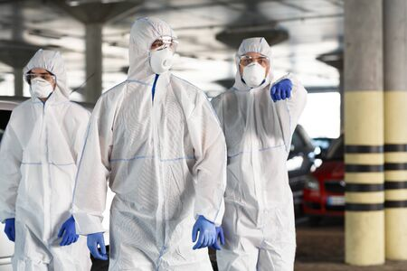 Time to protect yourself, stay at home. Men in hazmat suits pointing at you, epidemic, quarantine, copy space