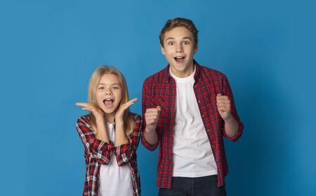 Siblings Cheering. Portrait Of Joyful Little Brother And Sister Raising Hands Yelling Shouting With Excitement Over Blue Background With Free Space