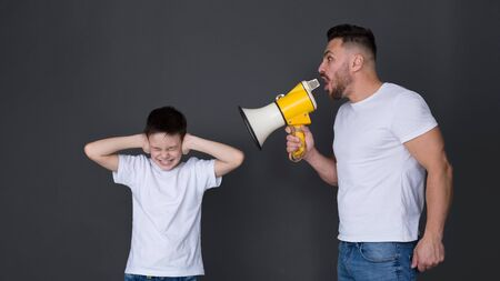 Family abusement. Nervous father screaming at son with megaphone, boy closing ears, dark studio background