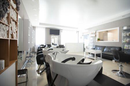 Focus on sink for washing hair. Beauty salon inside