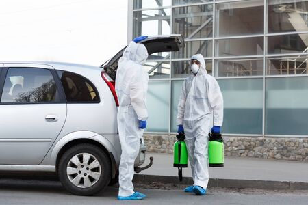 Stay at home. Man in hazmat suits buying disinfection spray for home cleaning, epidemic, quarantine, copy space Archivio Fotografico