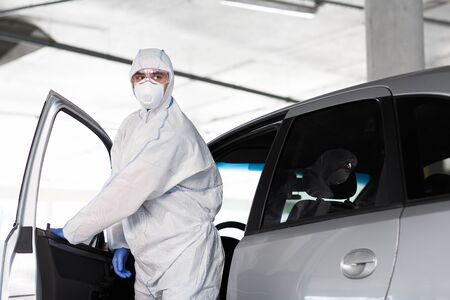 Man in hazmat suit get out of the car, coronavirus, quarantine, covid-19, world pandemic