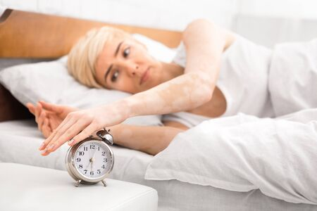 Middle aged woman waking up and turning off the alarm clock, blurred background, copy space 版權商用圖片