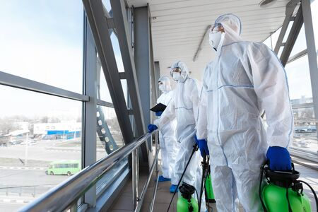 Medical workers in hazmat suits disinfecting with spray public places from coronavirus cells epidemic, pandemic health risk