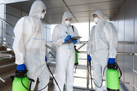 Men in virus protective suits disinfecting indoor accommodation, pandemic health risk, coronavirus