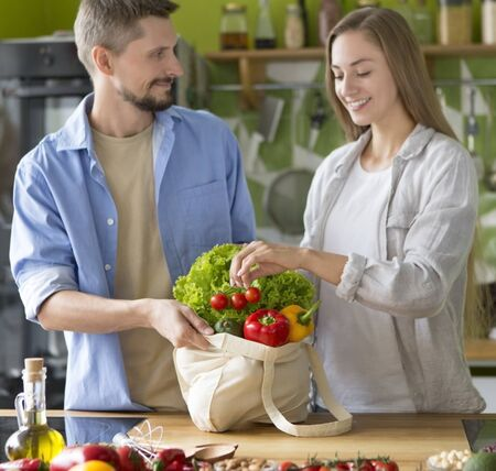 Young beautiful couple in kitchen cooking vegetarian healthy dishes together, quarantine time Archivio Fotografico