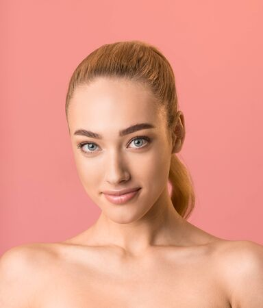Female Beauty Portrait. Beautiful Blonde Girl Smiling Looking At Camera Posing Over Pink Backgroound. Studio Shot, Vertical Standard-Bild