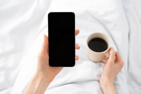 Woman using cell phone with blank screen in bed during morning time at home, drinking coffee, copy space