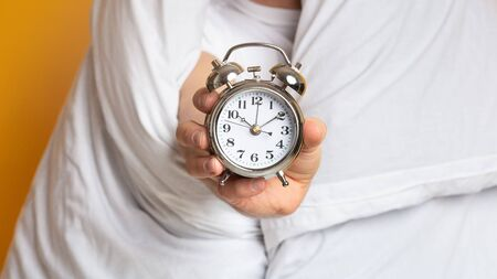 Man in blanket with an alarm clock, close up, free space 版權商用圖片