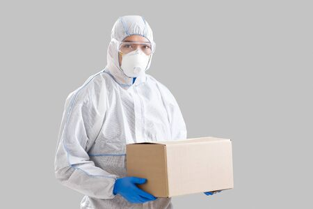 Humanitarian support. Asian man in protective suit with box in hands