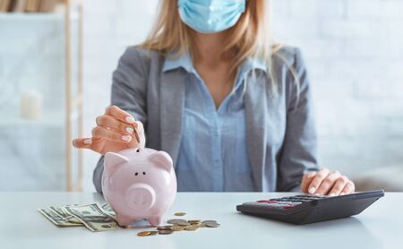Girl in protective mask saves money in bank pig during quarantine Stok Fotoğraf