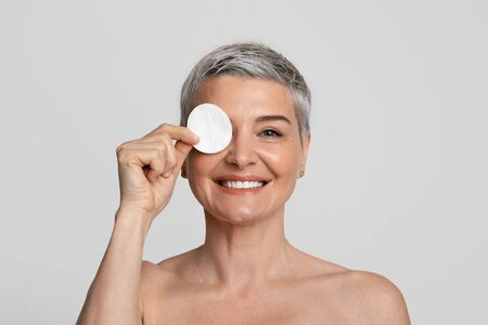 Remove makeup routine. Attractive middle-aged woman covering eye with cotton pad and smiling at camera, posing on light studio background Stock Photo