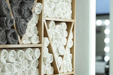 In interior at hairdresser, towels for clients on shelf, free space