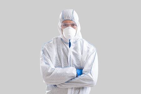 Coronavirus epidemic control concept. Asian man in protective suit, glasses and gloves with crossed arms Stock fotó