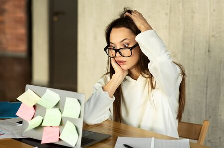 Freelance young woman shocked by tasks, searches information. Ponders on idea, scratches head Stock fotó