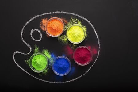 Dry paint in palette with drawn chalk isolated on black background