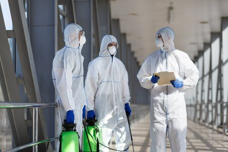 covid 19 epidemic, biohazard. Men in virus protective suits planning to disinfecting city with chemicals, copy space