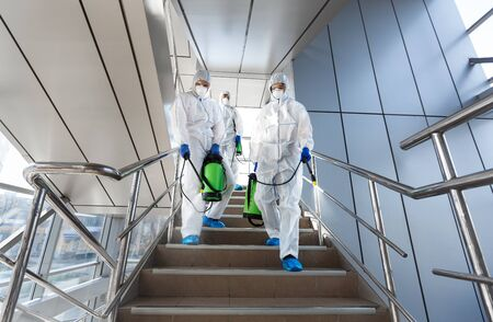 Government workers in protective suits making disinfection of stairs and surfaces from coronavirus, preventive measures, copy space
